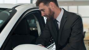 Der stilvolle Mann wählt neues Automobil gehend um Luxusauto und es im Auto-Vertragshändler berührend Reiche Leute stock video