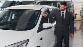 Der stilvolle Mann wählt neues Automobil gehend um Luxusauto und es im Auto-Vertragshändler berührend Reiche Leute stock video footage