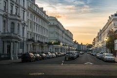 Der Straßen-Ansicht Londons Chelsea weiße Häuser mit Autos bei Sonnenuntergang Lizenzfreie Stockfotos