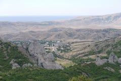 Der Straßenlauf zwischen den grünen Steigungen der Berge zu einem kleinen Dorf, das im Tal liegt In einer Umwelt lizenzfreie stockfotografie