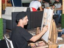 Der Straßenmaler sitzt auf einem Stuhl am Abend und zeichnet einen Bleistift ein Paar, das für ihn in Naharija, Israel aufwirft Lizenzfreie Stockfotos