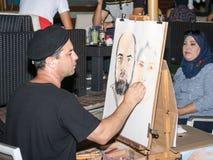 Der Straßenmaler sitzt auf einem Stuhl am Abend und zeichnet einen Bleistift ein Paar, das für ihn in Naharija, Israel aufwirft Stockbilder