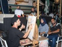Der Straßenmaler sitzt auf einem Stuhl am Abend und zeichnet einen Bleistift ein Paar, das für ihn in Naharija, Israel aufwirft Lizenzfreie Stockbilder