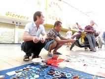 Der Straßenstall, alte Bücher und alte Münzen verkaufend Leute passen auf und kaufen Stockbilder