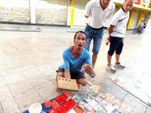Der Straßenstall, alte Bücher und alte Münzen verkaufend Leute passen auf und kaufen Stockbild