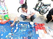 Der Straßenstall, alte Bücher und alte Münzen verkaufend Leute passen auf und kaufen Stockfotografie
