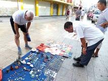 Der Straßenstall, alte Bücher und alte Münzen verkaufend Leute passen auf und kaufen Stockfotos