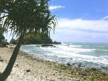 Der Strand ist von den Felsen voll und die weißen Wellen brechen in lizenzfreie stockbilder