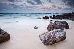 Der Strand mit großem Felsen im Vordergrund Stockbilder