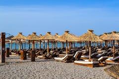 Der Strand mit Strohregenschirmen von der Sonne und weichen von den Sonnenruhesesseln Adriatischer Küste Sommer Ohne Leute Stockfoto