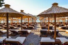 Der Strand mit Strohregenschirmen von der Sonne und weichen von den Sonnenruhesesseln Adriatischer Küste Sommer Ohne Leute Stockbilder
