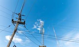 Der Strompfosten mit der elektrischen Linie und die Telekommunikation ragt hoch stockfotografie