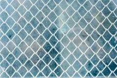 Der strukturierte Hintergrund einer gesponnenen flachen Masche hinter einem Blitzen Glas Blaues schmutziges Glas Weinlesekonzept  Lizenzfreies Stockfoto