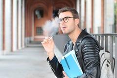 Der Student, der auf dem Campus raucht, schließen oben stockfoto