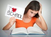 Der Student, der ein Zeichen mit den Wörtern hasse ich hält, Schule stockfotografie