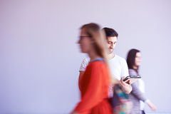 Der Student, der an Tablette arbeitet, Leute gruppieren vorbei überschreiten Lizenzfreies Stockfoto