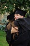 Der Student in einem schwarzes Kleidergraduierten umarmenden Mitschüler Stockfotografie