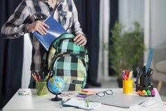 Der Student nimmt ein Notizbuch von seinem Rucksack stockfoto