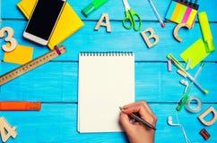 Der Student schreibt Stift in ein Notizbuch Beschneidungspfad eingeschlossen Flache Lage Schulbedarf in der Schulbank, Briefpapie Lizenzfreie Stockfotos