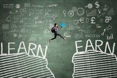 Der Student springend mit Text von Learn und von Earn lizenzfreie stockbilder