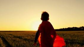 Der Superheld läuft auf einem grünen Rasen gegen den Hintergrund eines Sonnenuntergangs vortäuschend, in Zeitlupe zu fliegen stock video