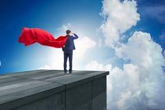 Der Superheldgeschäftsmann auf das Errichten bereit zur Herausforderung stockfotos