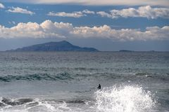 Der Surfer nimmt eine Welle, auf einem Surfbrett, Dias entlang der Welle, im Hintergrund des Berges, Sorrent Italien stockfotos