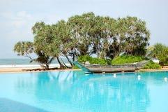 Der Swimmingpool und das alte traditionelle Boot Lizenzfreies Stockfoto