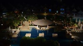 Der Swimmingpool und die Bar in der Nachtbeleuchtung im Luxushotel stock video