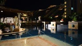 Der Swimmingpool und die Bar in der Nachtbeleuchtung im Luxushotel stock footage