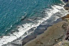 Der Türkis-blaue Atlantik mit weißen Wellen in einem Diagonalschnitt mit einem grauen feinen Strand stockbilder