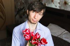 Der Tag der Frauen, der Kerl mit roten Tulpen Lizenzfreie Stockfotos