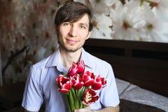 Der Tag der Frauen, der Kerl mit roten Tulpen Lizenzfreie Stockfotografie