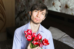 Der Tag der Frauen, der Kerl mit roten Tulpen Lizenzfreie Stockbilder