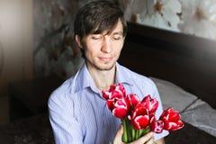 Der Tag der Frauen, der Kerl mit roten Tulpen Stockfotos