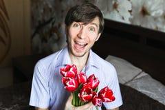 Der Tag der Frauen, der Kerl mit roten Tulpen Lizenzfreies Stockbild