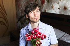 Der Tag der Frauen, der Kerl mit roten Tulpen Stockbild