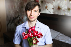 Der Tag der Frauen, der Kerl mit roten Tulpen Stockfoto