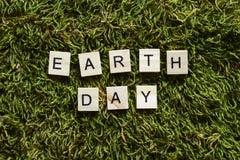 Der Tag der Erde, der mit hölzernen Buchstaben geschrieben wurde, berechnete der Form auf dem grünen Gras lizenzfreie stockbilder