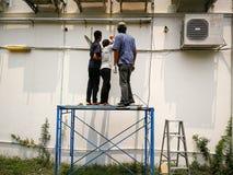 Der Techniker wird mit einem hängenden Stand für Klimaanlage ausgerüstet stockfotografie