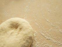 Der Teig und das Mehl auf einem hölzernen Brett Lizenzfreies Stockfoto
