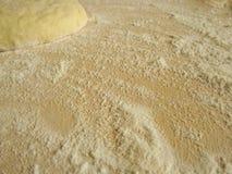 Der Teig und das Mehl auf einem hölzernen Brett Stockbild