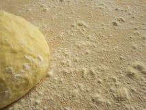 Der Teig und das Mehl auf einem hölzernen Brett Stockfoto