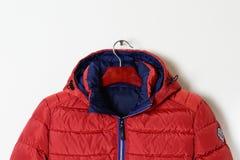 Der Teil einer hellen roten Jacke ist eine unten Jacke mit einer Haube und einem aufgeknöpften Kragen Lizenzfreie Stockbilder