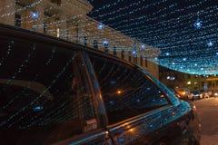 Der Teil einer Winterstraße beleuchtete durch Girlanden Stockfotografie