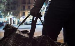 Der Terrorist, der schwarze Bombe steht und hält, bauschen sich in der Hand lizenzfreie stockbilder