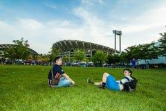 Der thailändische Fußballfan mit zwei Männern, der auf das Fußballspiel wartet Stockbild