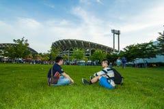 Der thailändische Fußballfan mit zwei Männern, der auf das Fußballspiel wartet Lizenzfreie Stockfotos
