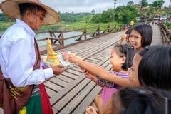 Der Thailändischmontag der Kinder sind gesetzte Geldangebote im Heiligen, das Almosen auf Montag-Brücke rollen Lizenzfreie Stockfotografie