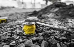 Der Thread, zum des Niveaus, vor der Platzierung des Kopfsteins, zu bestimmen und der Hammer liegen auf dem Schutt während des Bü lizenzfreie stockfotografie